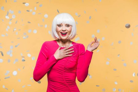 Foto de Surprised girl in red dress and white wig posing with holiday confetti, isolated on yellow - Imagen libre de derechos