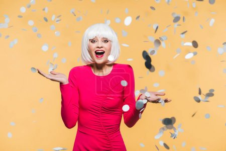 Foto de Excited girl in red dress and white wig posing with holiday confetti, isolated on yellow - Imagen libre de derechos
