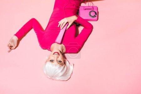 Photo pour Vue supérieure de la femme élégante dans la perruque blanche avec le téléphone rétro d'isolement sur le rose - image libre de droit