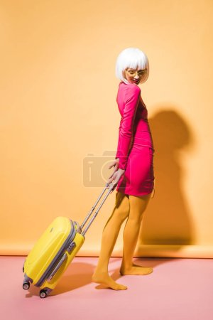 Photo for Fashionable woman posing with travel bag on yellow - Royalty Free Image