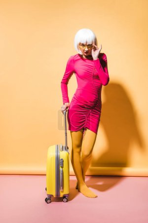 Photo for Beautiful stylish woman posing with travel bag on yellow - Royalty Free Image