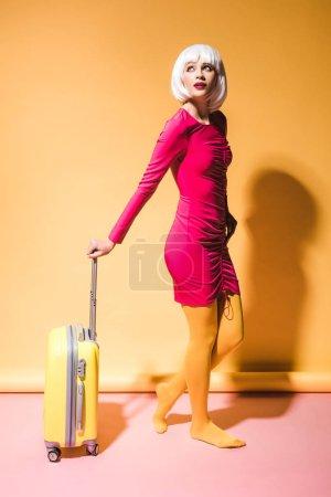 Photo pour Femme attirante posant avec la valise sur le jaune - image libre de droit
