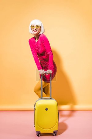 Photo pour Fille attirante à la mode posant avec la valise sur le jaune - image libre de droit