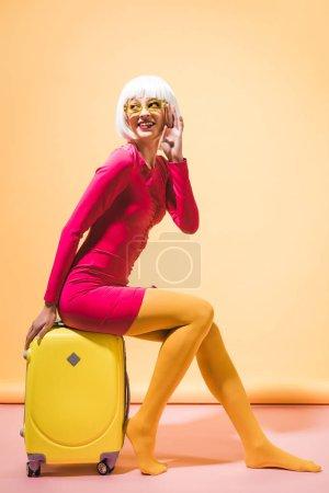 Photo pour Fille de sourire à la mode posant avec la valise sur le jaune - image libre de droit