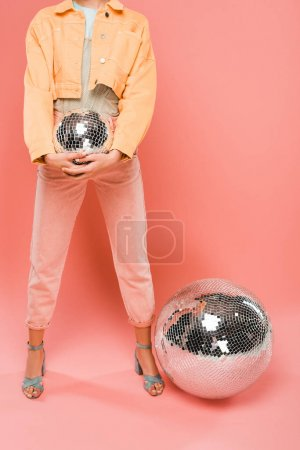 Photo pour Cropped view of fashionable girl holding disco ball on pink - image libre de droit
