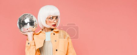 Photo for Fashionable girl in white wig and sunglasses posing with disco ball, isolated on pink - Royalty Free Image