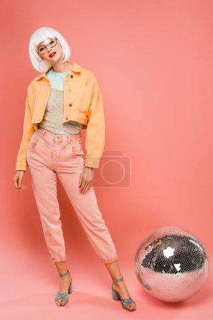 Photo pour Belle fille dans la perruque blanche posant près de la boule de disco sur le rose - image libre de droit