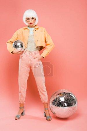 Photo pour Fille élégante dans la perruque blanche posant avec des boules de disco sur le rose - image libre de droit