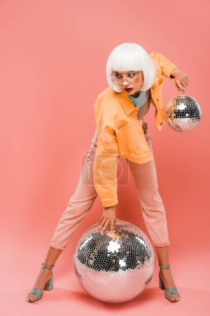 Photo for Fashionable woman in white wig posing with disco balls on pink - Royalty Free Image