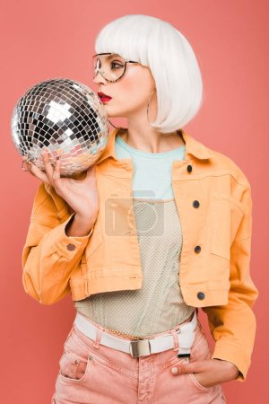 Photo for Stylish girl in white wig posing with disco ball, isolated on pink - Royalty Free Image