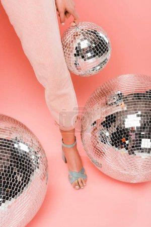Photo pour Vue partielle de fille élégante posant avec des boules de disco sur le rose - image libre de droit