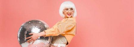 Photo pour Fille à la mode heureuse dans la perruque blanche posant avec la bille de disco, d'isolement sur le rose - image libre de droit