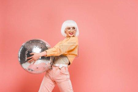 Photo pour Fille de sourire à la mode dans la perruque blanche posant avec la bille de disco, d'isolement sur le rose - image libre de droit