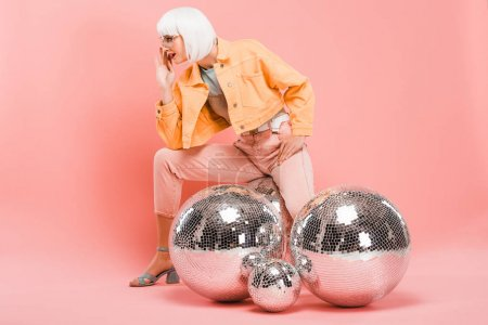 Photo for Stylish girl in white wig posing with disco balls on pink - Royalty Free Image