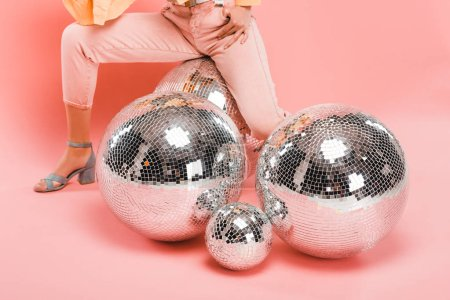 partial view of trendy girl posing with disco balls on pink