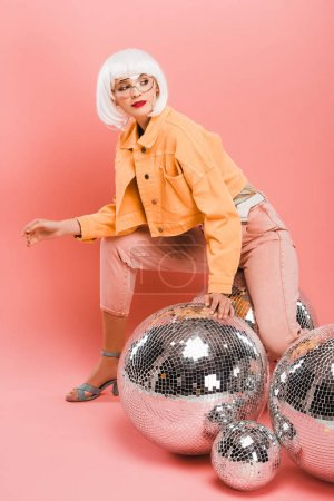 Photo pour Fashionable girl in white wig posing with disco balls on pink - image libre de droit