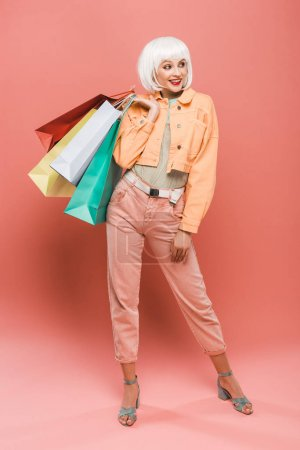 Photo for Attractive smiling girl in white wig with shopping bags on pink - Royalty Free Image