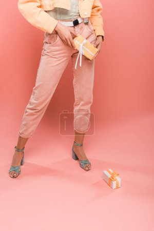 Photo for Cropped view of stylish woman with gifts on pink - Royalty Free Image