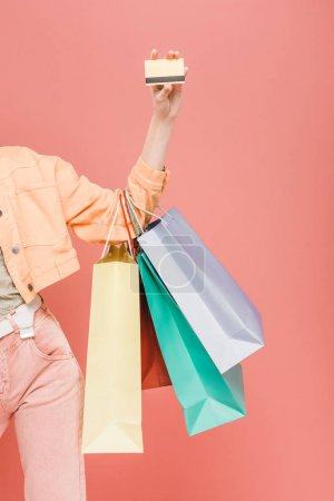 Photo for Cropped view of girl with shopping bags and credit card, isolated on pink - Royalty Free Image