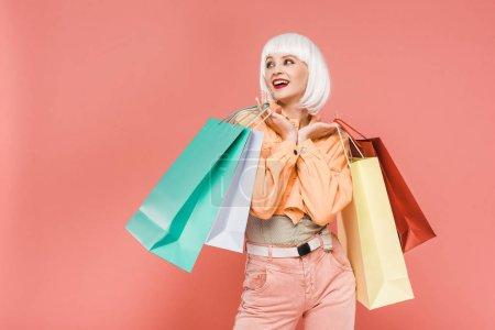 Photo pour Femme à la mode dans la perruque blanche avec des sacs à provisions, d'isolement sur le rose - image libre de droit