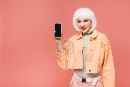 Photo pour Belle femme montrant smartphone avec écran blanc, isolé sur rose - image libre de droit