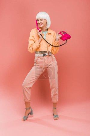 Photo pour Fille à la mode heureuse dans la perruque blanche parlant sur le téléphone de cru sur le rose - image libre de droit