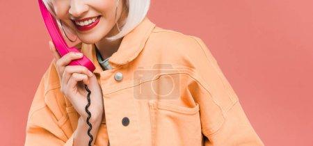 Photo pour Vue recadrée de fille élégante dans la perruque blanche parlant sur le téléphone rétro, d'isolement sur le rose - image libre de droit