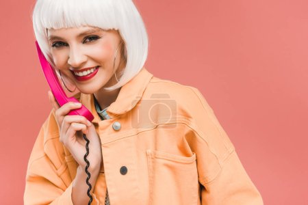 Photo for Happy stylish woman in white wig talking on vintage telephone, isolated on pink - Royalty Free Image