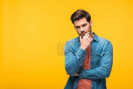 Photo pour Beau homme pensif touchant le menton isolé sur le jaune - image libre de droit