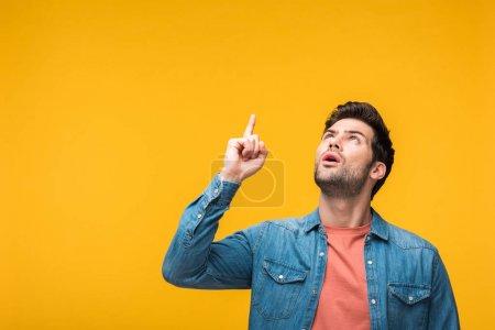 Photo pour Homme beau confondu pointant avec le doigt isolé sur le jaune - image libre de droit
