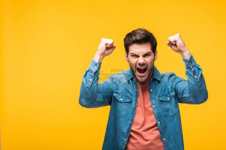 Photo for Excited handsome man gesturing with hands isolated on yellow - Royalty Free Image