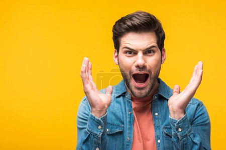 Photo for Surprised handsome man gesturing with hands isolated on yellow - Royalty Free Image