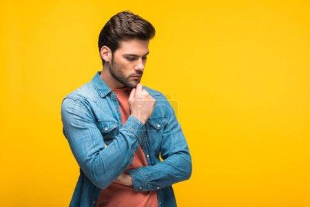 Photo pour Beau homme pensif touchant le menton isolé sur le jaune avec l'espace de copie - image libre de droit