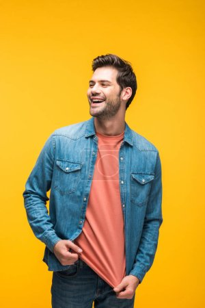 Photo for Laughing good-looking man looking away isolated on yellow - Royalty Free Image