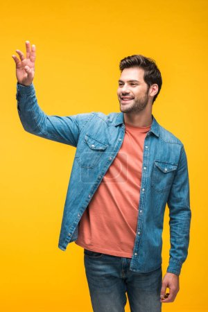 Photo for Handsome man gesturing with hand and smiling isolated on yellow - Royalty Free Image