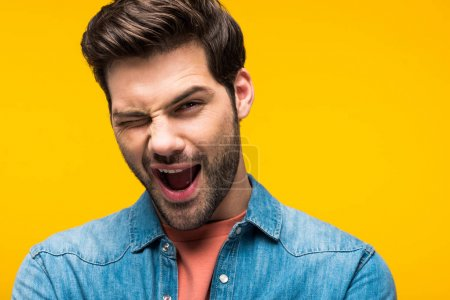 Photo for Excited handsome man winking and looking at camera isolated on yellow - Royalty Free Image