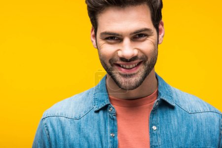 smiling good-looking man looking at camera isolated on yellow