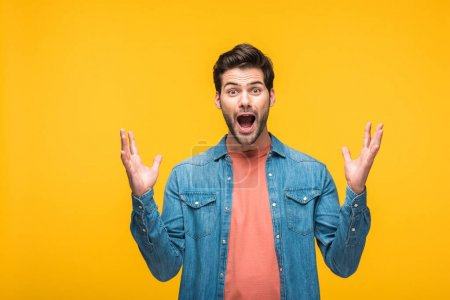 Photo for Excited handsome man gesturing with hands and looking at camera isolated on yellow - Royalty Free Image