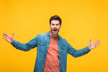 Photo for Handsome excited man gesturing with open palms isolated on yellow - Royalty Free Image