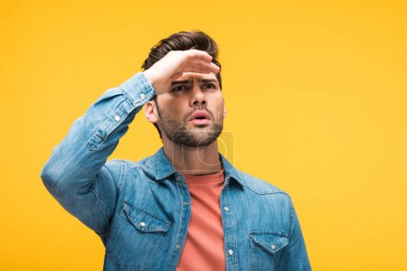 confused handsome man with hand on forehead isolated on yellow