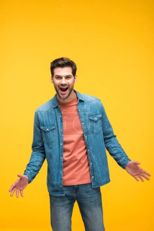 Photo for Excited handsome man with open palms isolated on yellow - Royalty Free Image