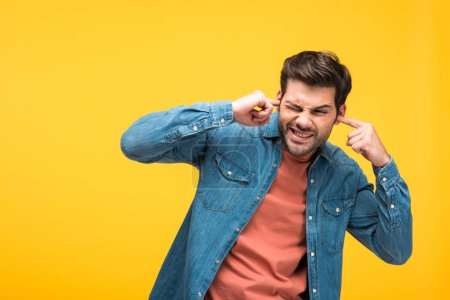 Photo for Dissatisfied handsome man plugging ears with fingers isolated on yellow - Royalty Free Image