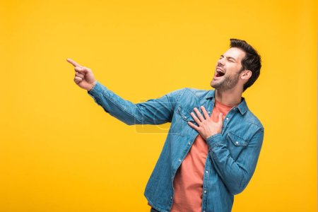 Photo for Good-looking man laughing and pointing with finger isolated on yellow - Royalty Free Image