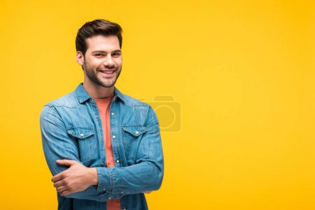 smiling handsome man with crossed arms isolated on yellow with copy space