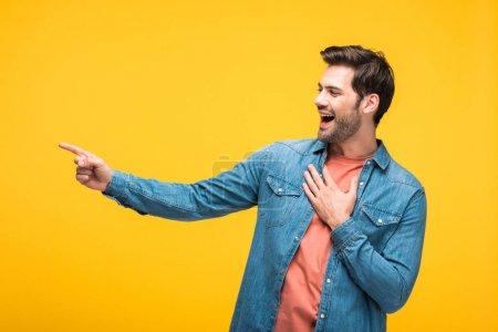 Photo pour Bel homme riant et pointant avec le doigt isolé sur le jaune - image libre de droit