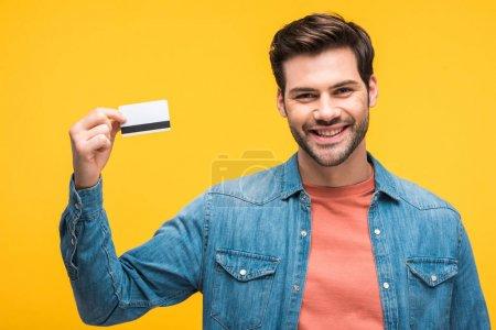 Photo pour Bel homme souriant tenant la carte de crédit isolé sur jaune - image libre de droit