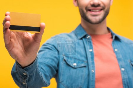 cropped view of man holding credit card with copy space isolated on yellow