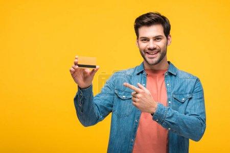 Photo pour Heureux bel homme pointant avec le doigt à la carte de crédit isolé sur jaune - image libre de droit