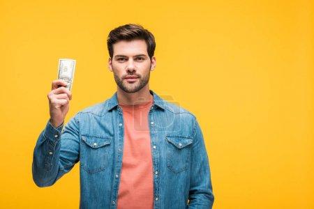 Photo pour Bel homme tenant de l'argent isolé sur jaune avec de l'espace de copie - image libre de droit