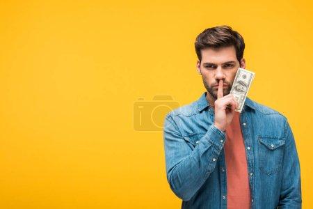 Photo pour Bel homme faisant geste de silence et tenant l'argent isolé sur jaune - image libre de droit